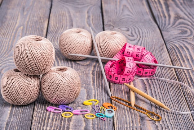 Balls of yarn, knitting needles, measuring tape and clips on wooden background