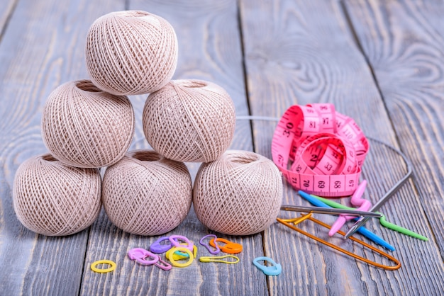 Balls of yarn, knitting needles, measuring tape and paper clips on wooden background