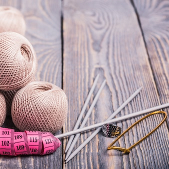 Balls of yarn, knitting needles and measuring tape on a wooden background.