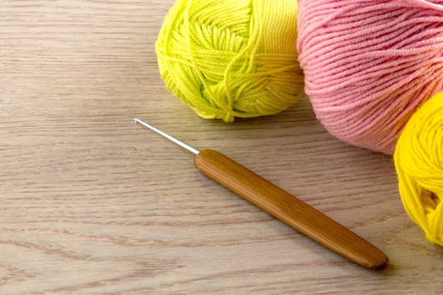 Balls of yarn, knitting needles, on wooden table