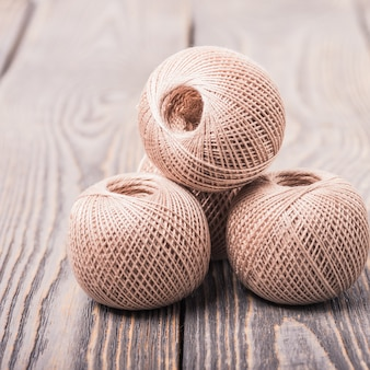 Balls of yarn thread for knitting on a wooden background.
