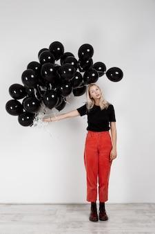 Молодая красивая белокурая девушка держа черные baloons над белой стеной.