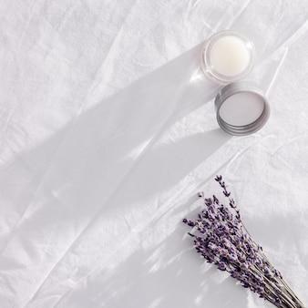 Бальзам с эфирным маслом лаванды и сухими цветами на белом постельном белье. аромат лаванды улучшает сон и избавляет от бессонницы. красивый вечерний свет.