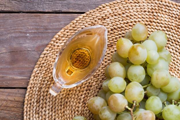 ガラスの水差し、ヴィンテージの木製の表面、素朴なスタイルのバルサミコ酢、