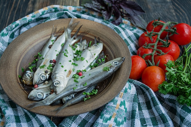 Baltic herring seafood. salted herring fish in a bowl with spices and herbs.