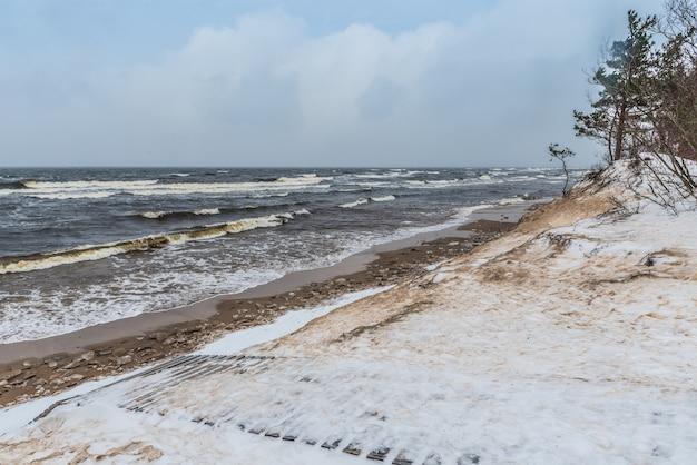 バルト海のビーチは冬は雪が降り、海には大きな波があります。ラトビアのサウルクラスチにある冬のバルト海の砂丘の間の小道