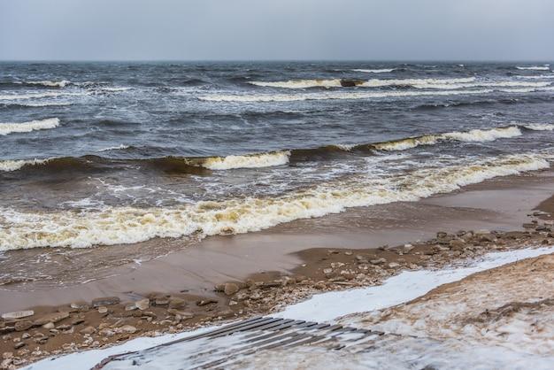 Пляж балтийского моря зимой снежный, а в море большие волны. пешеходная дорожка между зимними дюнами балтийского моря в саулкрасты в латвии