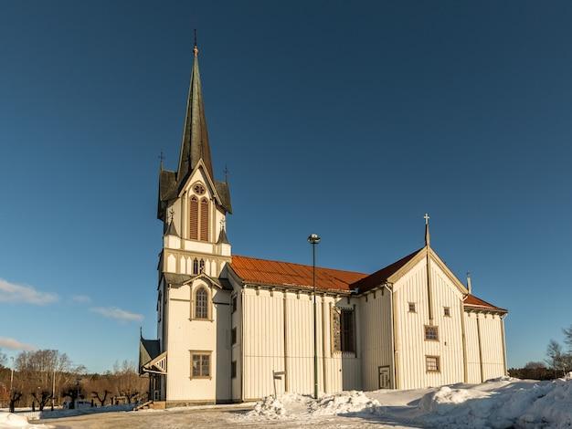 Bamble church, большая деревянная церковь buildt в 1845 году. зима, снег, солнце и голубое небо. вид сбоку. горизонтальное изображение.