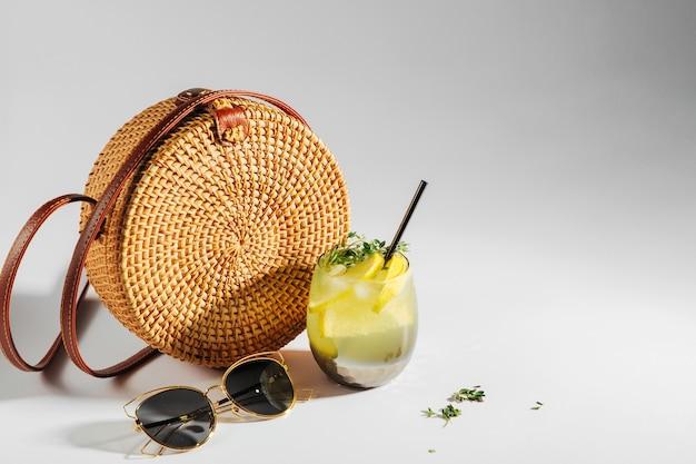 그림자와 함께 흰색 바탕에 선글라스와 레모네이드 유리 대나무 가방