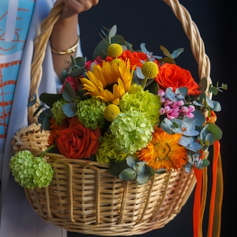 A bamboo basket of sunflowers, red roses an carnations