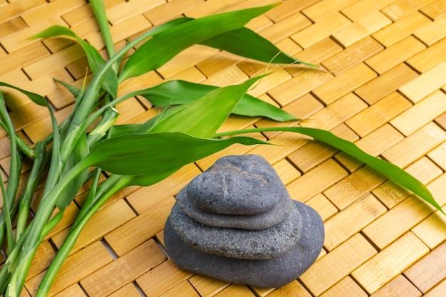 木製のマットの上に竹の枝と黒い石のピラミッド。