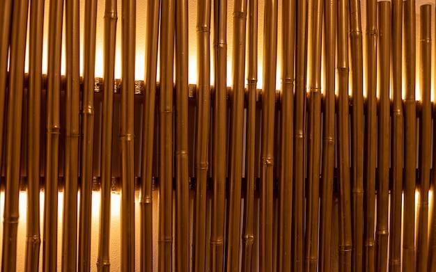 Бамбуковые ветки окрашены в золотые тона с подсветкой. настенный декор, светильник. полный кадр крупным планом. бамбуковые стволы с подсветкой в интерьере. место для текста. абстрактный фон и текстура.