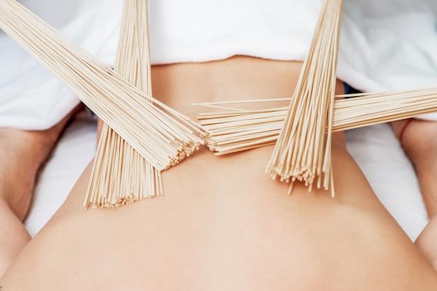 Бамбуковые веники на спине молодого человека во время массажа в четыре руки