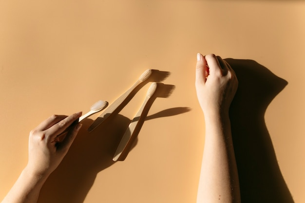 Bamboo brushes in the hands of the girl wastefree spa ecofriendly bathroom accessories