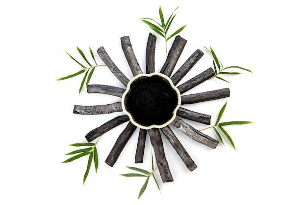 竹炭、緑の葉と白い背景で隔離の粉末。上面図、フラットレイ。