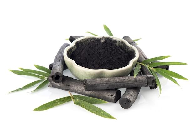 竹炭、緑の葉と白い背景で隔離の粉。