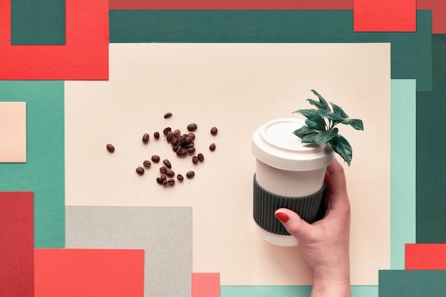 竹のコーヒーカップ。カップを保つか、抽象的な幾何学的な層状の多色の長方形の紙の壁に女性の手でマグカップを旅行します。創造的なフラットレイアウト、上面図、環境に優しいゼロ廃棄物カップ。