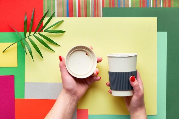 ヤシの葉と抽象的な幾何学的な多色の長方形の紙の背景に女性の手でふた付き竹コーヒーカップ。廃棄物ゼロの生分解性カップを備えた創造的なフラットレイアウト。