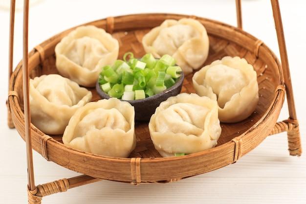 白い背景で隔離の中国の蒸しラビオリ餃子shuijiaoと竹料理