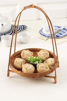 白い背景の上の中国の蒸しラビオリ餃子shuijiaoと竹料理。テキストまたは広告用のコピースペース