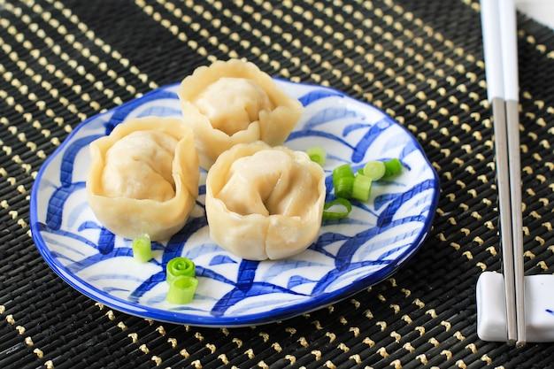 箸で中華蒸しラビオリ餃子水家尾を添えた竹料理。選択されたフォーカス