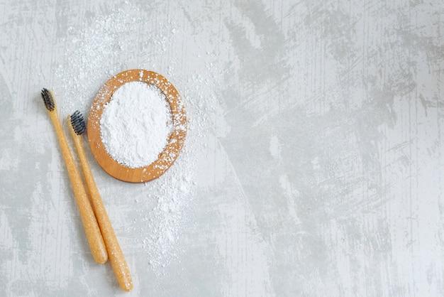 Бамбуковые экологически чистые зубные щетки и зубной порошок, чистка зубов без отходов на бетонном фоне