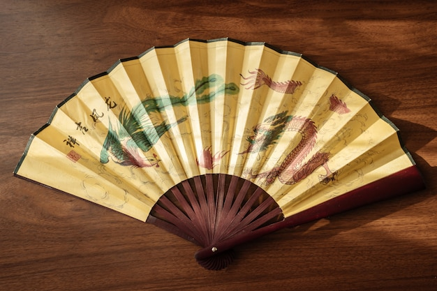 Bamboo fan with a dragon pattern on a wooden background