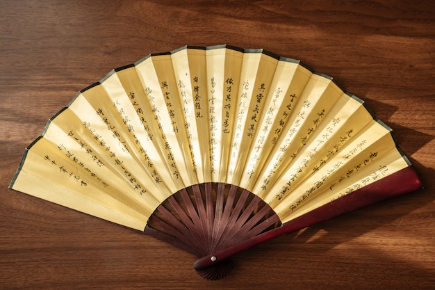 Bamboo fan with hieroglyphs on a wooden background