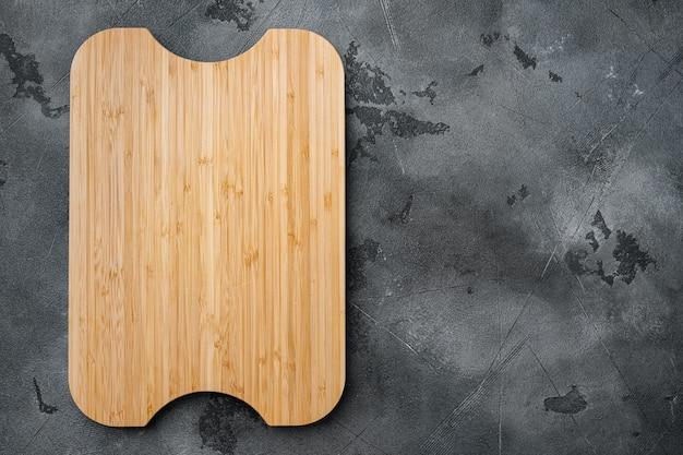 대나무 주방 커팅 보드는 텍스트나 음식을 복사할 수 있는 빈 공간으로 설정되어 있으며, 회색 석재 테이블 배경 위에 평평한 평면이 놓여 있습니다.
