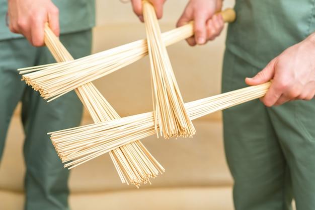 Бамбуковые массажные веники в руках двух массажистов.