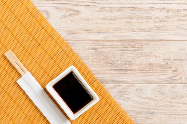 Бамбуковая циновка и соевый соус с палочками для суши на деревянном столе. вид сверху с копией космического фона для суши. плоская планировка.