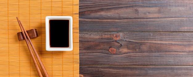 Бамбуковая циновка и соевый соус с палочками для суши на деревянном столе