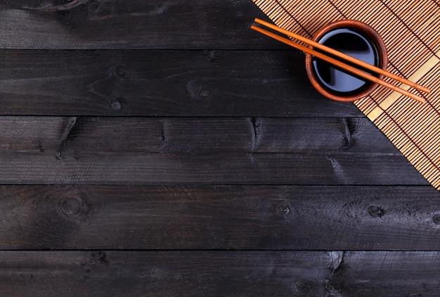 Бамбуковая циновка, соевый соус, палочки для еды на темном столе