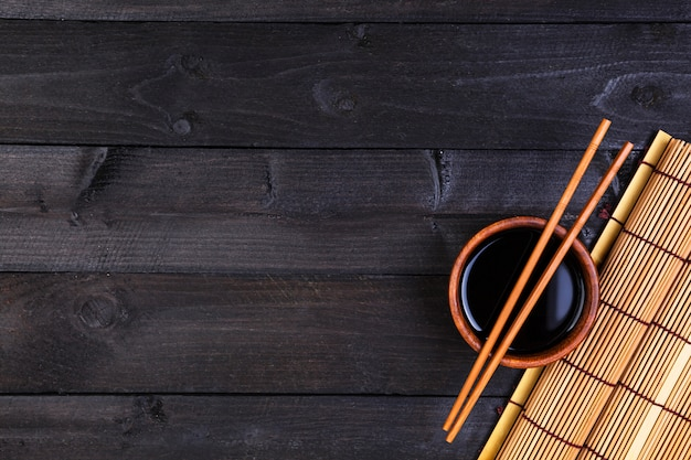 Bamboo mat and soy sauce on dark wooden table. top view