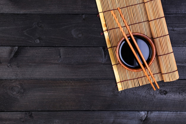 Bamboo mat and soy sauce on dark wooden table.