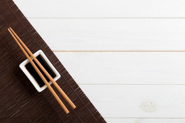Bamboo mat and soy sauce with sushi chopsticks on white wooden table.