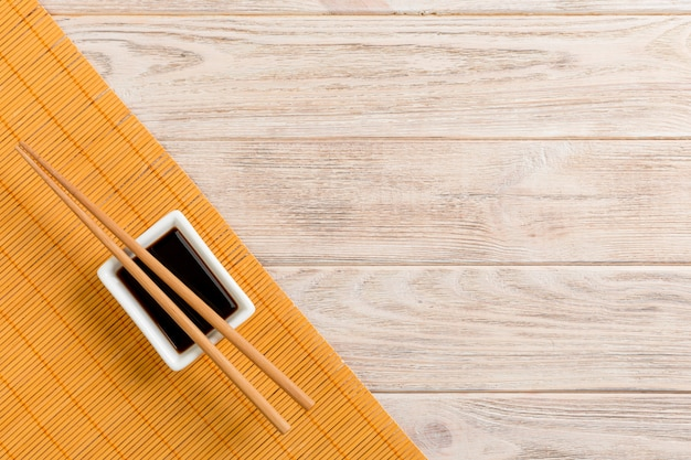 Bamboo mat and soy sauce with sushi chopsticks on wooden table. top view with copy space background for sushi. flat lay