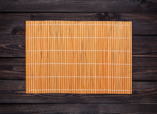 Bamboo mat on a wooden table, top view