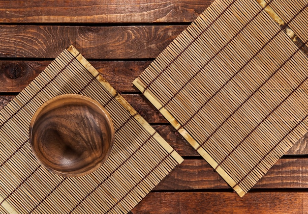 Bamboo mats with wooden bowl on wooden table