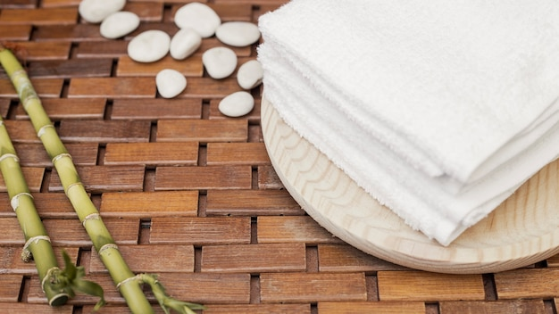 Bamboo plant; towel and pebbles on wooden background