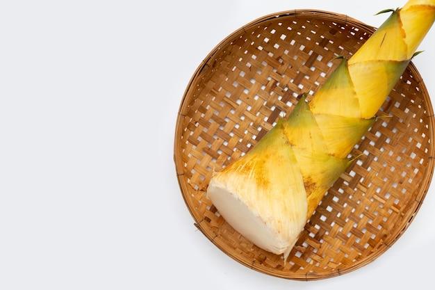 白い背景の上の竹かごでタケノコ。