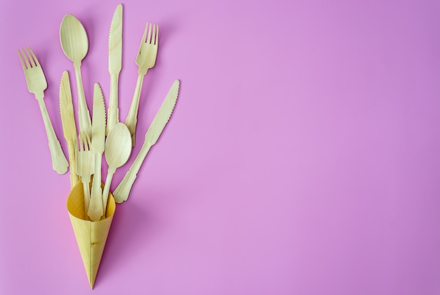 Bamboo spoon and fork in a row on pink or violet background