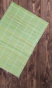 Bamboo tablecloth on wooden table over grunge.