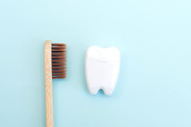 青い背景に白い歯の形をした竹の歯ブラシと白いデンタルフロス。