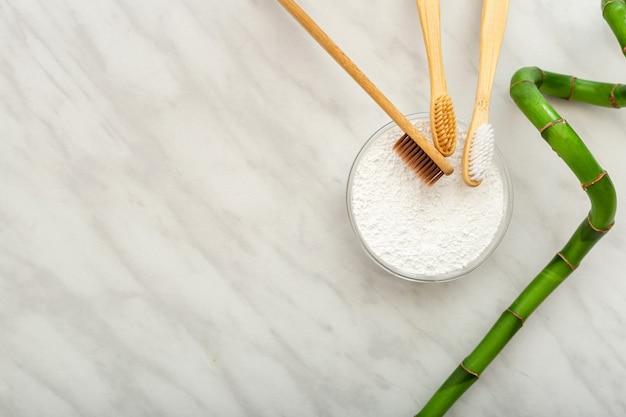 Бамбуковая зубная щетка, зубной порошок для чистки зубов из бамбуковых растений на белом мраморном фоне. плоская копия пространства. биоразлагаемая зубная щетка из натурального бамбука. экологически чистая, без отходов, стоматологическая помощь.
