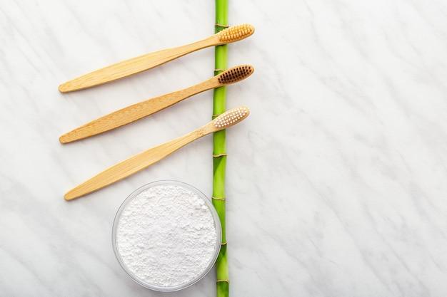 竹の歯ブラシ、白い大理石の背景に竹の植物歯磨剤の歯の粉末。フラットレイコピースペース。生分解性の天然竹の歯ブラシ。環境にやさしい、ゼロ廃棄物、歯科医療プラスチックフリーのコンセプト。