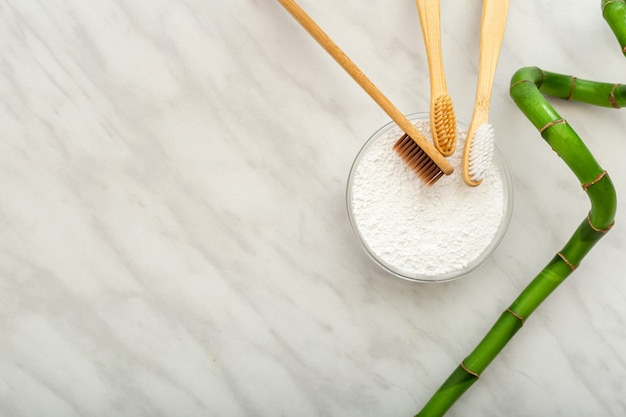 Bamboo toothbrush, bamboo plant dentifrice tooth powder on white marble background.flat lay copy space.biodegradable natural bamboo toothbrush.eco friendly,zero waste,dental care plastic free concept.