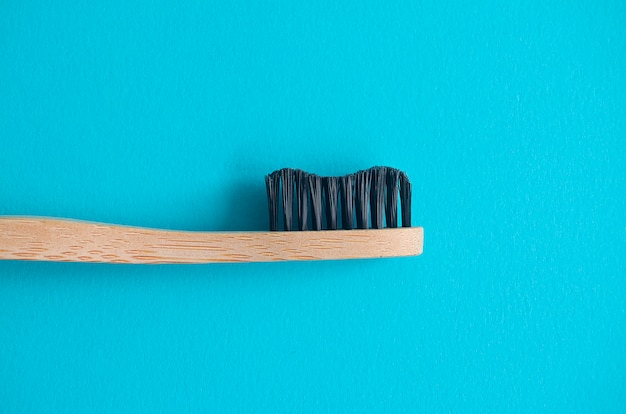 Бамбуковая зубная щетка крупным планом на синем фоне