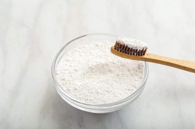 竹の歯ブラシ、白い大理石の背景に歯磨き粉。生分解性の天然竹歯ブラシ。環境にやさしい、ゼロウェイスト、デンタルケアプラスチックフリーのコンセプト。閉じる