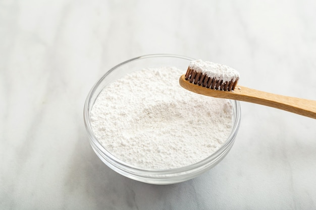 Bamboo toothbrush, dentifrice tooth powder on white marble background. biodegradable natural bamboo toothbrush. eco friendly, zero waste, dental care plastic free concept. close up
